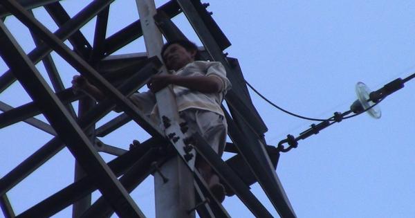 Người đàn ông trèo lên đỉnh trụ điện cao thế rồi múa và la hét