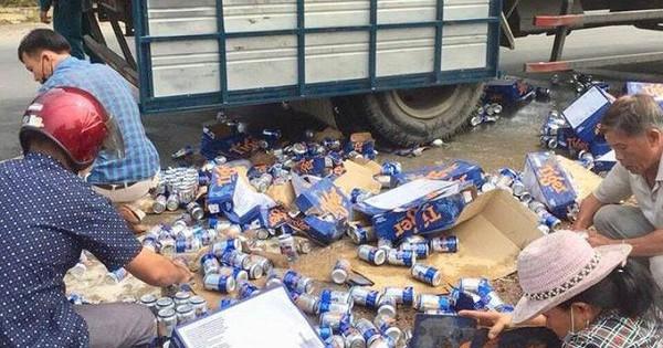 Người dân giúp tài xế thu gom bia rơi xuống đường