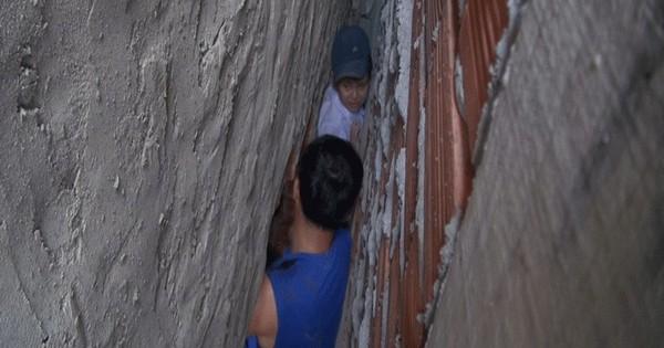 Bé trai 7 tuổi rượt đuổi mèo mắc kẹt sâu giữa hai tường nhà