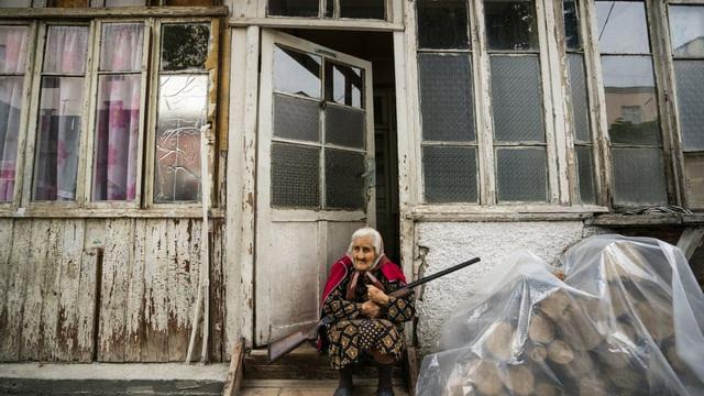 7 ngày qua ảnh: Cụ bà ngồi ôm súng trước nhà tại vùng chiến sự