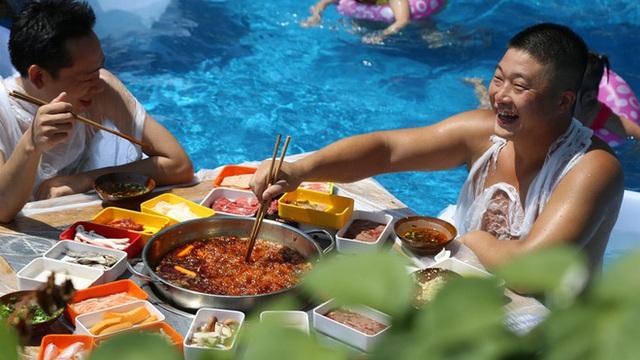 Thời tiết nóng nực, người dân Trung Quốc tràn xuống bể bơi ngồi ăn lẩu siêu cay