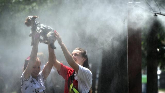 24h qua ảnh: Các cô gái giải nhiệt dưới vòi phun sương giữa trời nắng nóng