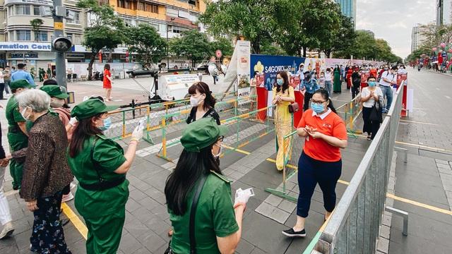 """Ảnh: Người Sài Gòn xếp hàng đo thân nhiệt, đeo khẩu trang vào """"check in"""" đường hoa Nguyễn Huệ"""