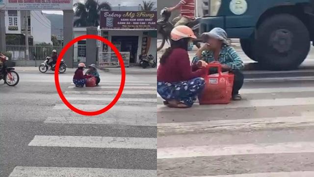 Mặc kệ xe cộ qua lại, 2 người phụ nữ ngồi xổm giữa đường buôn chuyện với nhau