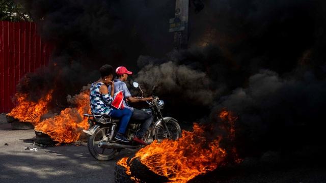 """24h qua ảnh: Người biểu tình lái môtô xuyên qua """"rào chắn lửa"""" từ lốp xe"""