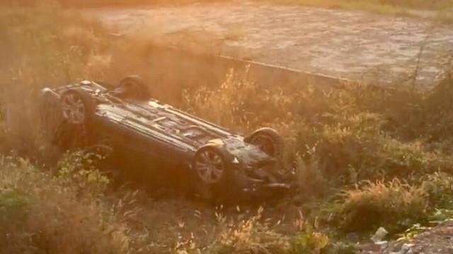 Ô tô 4 chỗ phơi bụng dưới bãi đất trống, người dân phá cửa cứu tài xế